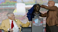 Ed Sabol, left, looks on as his son, Steve, unveils a bust of Ed during the induction ceremony at the Pro Football Hall of Fame, Saturday, Aug. 6, 2011, in Canton, Ohio. (AP Photo/Ron Schwane)