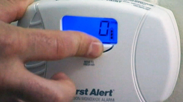 A person turns on a carbon monoxide detector.