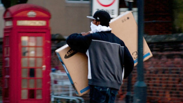 A British looter is seen walking away with a flat screen TV in this image taken from the blog 'Catch a Looter'.