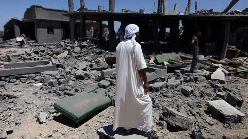 In this photo taken on a government-organized tour, a man stands in front of a destroyed home after it was allegedly hit by a NATO bomb in the town of Majar, near Zliten, Libya, Tuesday, Aug. 9, 2011. (AP / Dario Lopez-Mills)