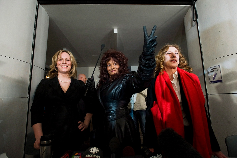 Terri-Jean Bedford makes a victory sign during a press conference, with Nikki Thomas, left, and Valerie Scott, right, in Toronto on Monday March 26, 2012. (Aaron Vincent Elkaim / THE CANADIAN PRESS)