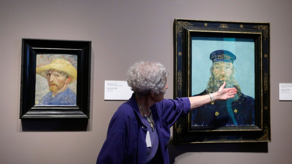 Detroit Institute of Arts docent Lea Schelke points out details in the Portrait of Postman Roulin by Van Gogh displayed at the museum in Detroit, June 13, 2013. (AP / Carlos Osorio)