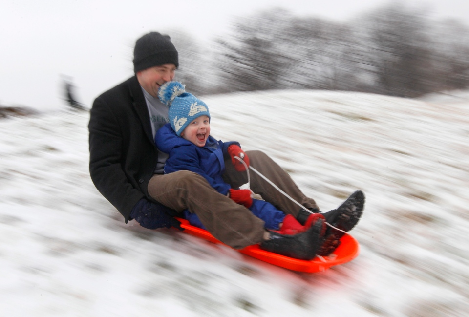 Matt Redmond, 3, and his father, Mike, ride a sled down a hill after an overnight snowfall in Baltimore, Saturday, Jan. 21, 2012. (AP / Patrick Semansky)