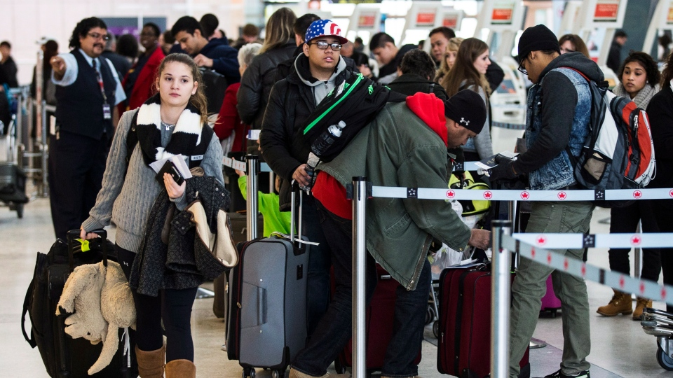 Travellers line up to check in at Pearson International Airport on Friday, Dec. 20, 2013. (The Canadian Press/Mark Blinch)