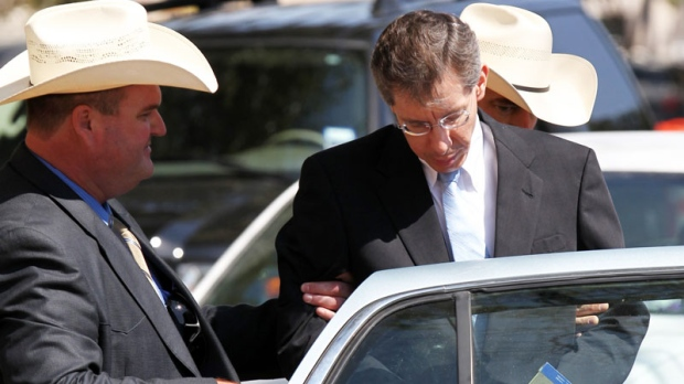 Warren Jeffs, leader of the Fundamentalist Church of Jesus Christ of Latter Day Saints, right, is placed into the back of a waiting car in San Angelo, Texas Tuesday, Aug. 9, 2011. (AP / The San Angelo Standard-Times, Patrick Dove)