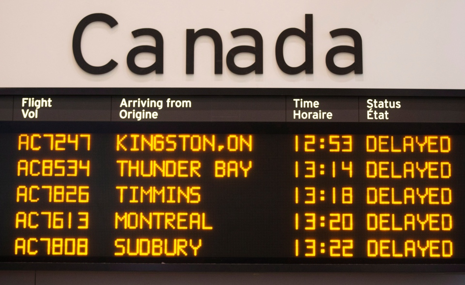 A sign showing delayed flight arrivals is seen at Pearson International Airport, where more travellers pass though the airport than usual for the holiday season, in Toronto Friday Dec.r 20, 2013. (Mark Blinch / THE CANADIAN PRESS)