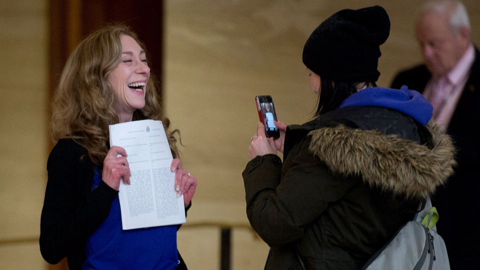 Valerie Scott holds up a copy of the ruling issued by the Supreme Court of Canada striking down the country's prostitution laws at the Supreme Court of Canada in Ottawa, Friday Dec. 20, 2013. (Adrian Wyld / THE CANADIAN PRESS)