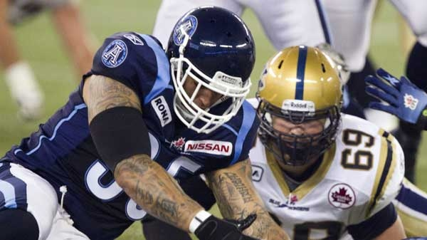 Toronto Argonauts linebacker Kevin Eiben (left) scoops up a fumble in front of Winnipeg Blue Bombers offensive lineman Glenn January (69) during first half CFL action in Toronto on Saturday, July 23, 2011. (Frank Gunn / THE CANADIAN PRESS)