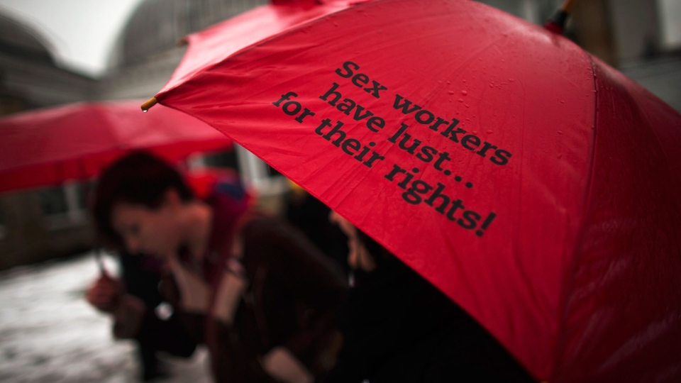 A woman holds a red umbrella, that are used as a symbol for sex workers rights, that reads 'Sex Workers have their lust for their rights!' during a rally at Allan Gardens park to support Toronto sex workers and their rights in Toronto, Friday, Dec. 20, 2013. (Mark Blinch / THE CANADIAN PRESS)