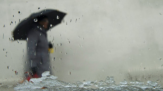 A pedestrian walks with an umbrella in freezing rain in this file photo. (The Canadian Press)
