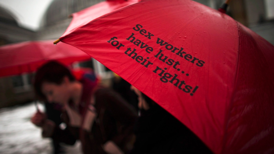 A woman holds a red umbrella, that are used as a symbol for sex workers rights, that reads 'Sex Workers have their lust for their rights!' during a rally at Allan Gardens park to support Toronto sex workers and their rights in Toronto, Friday December 20, 2013.(Mark Blinch /  THE CANADIAN PRESS)