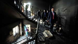 In this Nov. 26, 2012 file photo, Bangladeshi officials inspect the burned out Tazreen Fashions Ltd. garment factory on the outskirts of Dhaka, Bangladesh. (AP Photo)