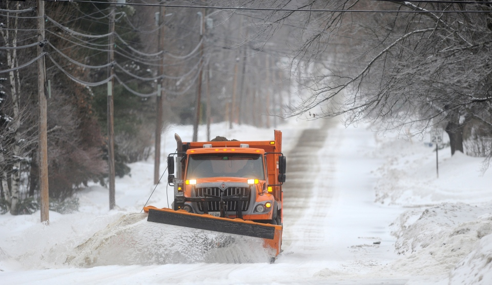 A Waterville Public Works snowplow clears Mayflower Hill Drive as a major ice storm rolls through Waterville, Maine, on Sunday morning, Dec. 22, 2013. (The Central Maine Morning Sentinel /  Michael G. Seamans)