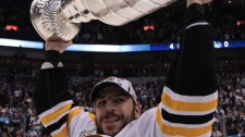 Boston Bruins' Milan Lucic hoists the cup following his team's win over the Vancouver Canucks in game 7 of NHL Stanley Cup Final hockey at Rogers Arena in Vancouver, Wednesday, June 15, 2011. (THE CANADIAN PRESS/Jonathan Hayward)
