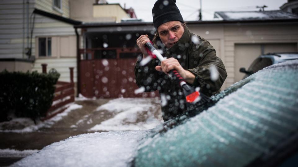 John Szücs scrapes the ice off his car near Dufferin Grove Park in Toronto on Sunday, Dec. 22, 2013 following ice storm. (Ian Willms / THE CANADIAN PRESS)