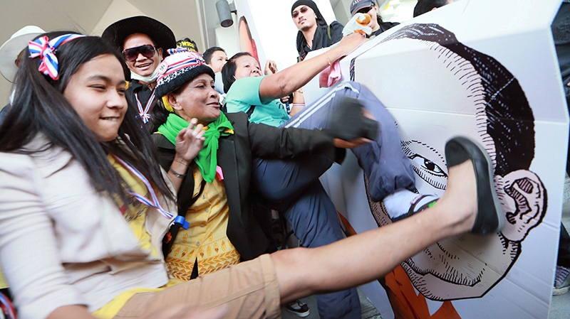 Thai anti-government protesters kick and hit at the drawing of Tharit Pengdit, chief of the Department of Special Investigation (DSI), after storming into his office during a rally in Bangkok, Thailand, Monday, Dec. 23, 2013. (AP / Wason Wanichakorn)