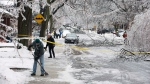 Pedestrians clear the sidewalks on a closed off Soudan Ave. in Toronto after an ice storm caused havoc knocking down trees and power lines in much of the city on Sunday, Dec. 22, 2013. (Aaron Vincent Elkaim / THE CANADIAN PRESS)