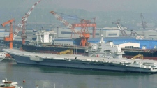 In this Aug. 5, 2011 photo a Chinese aircraft carrier, which had been under refurbishment, is at anchor at Dalian port in northeast Liaoning province. (AP / Kyodo News)