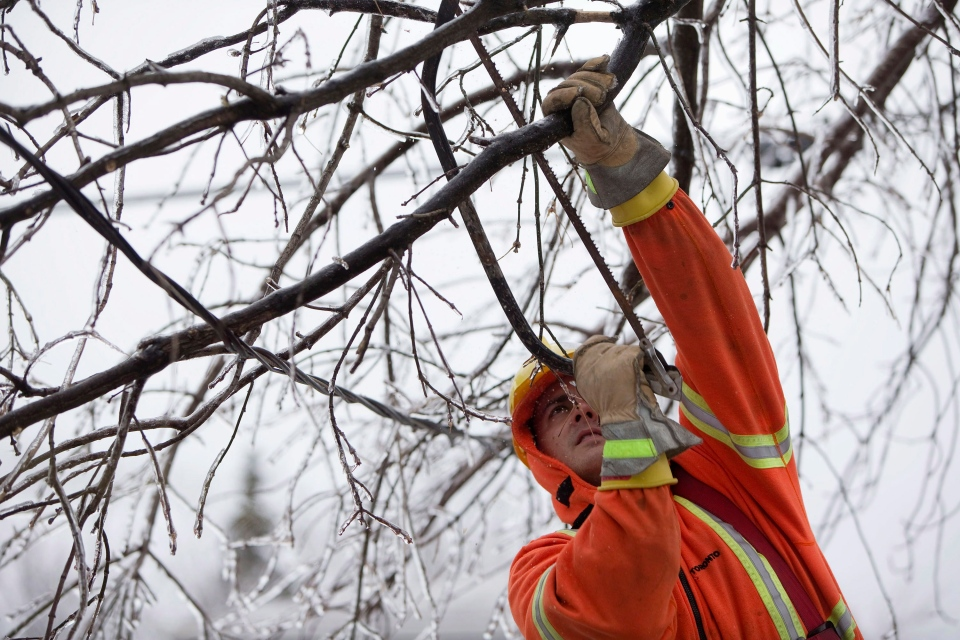 A worker from Stacey Electric, which was subcontracted to assist with restoring power following an ice storm in Toronto, works on a power line near Danforth Ave. and Victoria Park Ave. on Monday, Dec. 23, 2013. (Matthew Sherwood / THE CANADIAN PRESS)