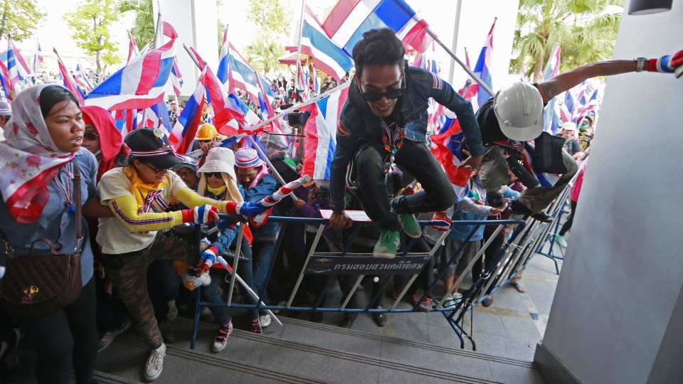 Anti-government protesters jump over the fence during a rally at the Department of Special Investigation (DSI) on the outskirts of Bangkok, Thailand, Monday, Dec. 23, 2013. (AP / Wason Wanichakorn)