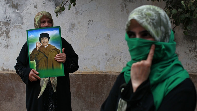 In this photo taken on a government-organized tour a woman holds up an image of Libyan leader Moammar Gadhafi during a protest in front of the Hungarian embassy in Tripoli, Libya, Thursday, Aug. 11, 2011. (AP Photo/Dario Lopez-Mills)