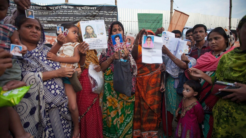 Relatives of the victims of the April 24 Rana Plaza building collapse display photographs of their friends and relatives as they gather to pay tributes at the venue of the tragedy at Savar, on the outskirts of Dhaka, Bangladesh, Thursday, Oct. 24, 2013.  (AP /  Suvra Kanti Das)