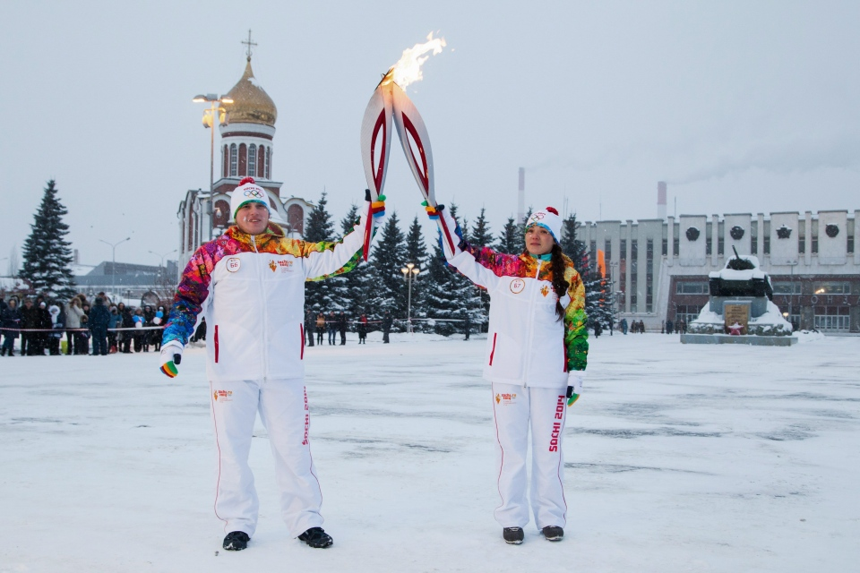 Torch bearers Yegor Klimov and Anna Usatova pose with Olympic torches in a square in front of the Uralvagonzavod tank factory, with a famous Soviet made tank T-34 on the right, during the Olympic torch relay in Russia's industrial Urals town of Nizhny Tagil, Friday, Dec. 13, 2013. (Olympictorch2014.com)