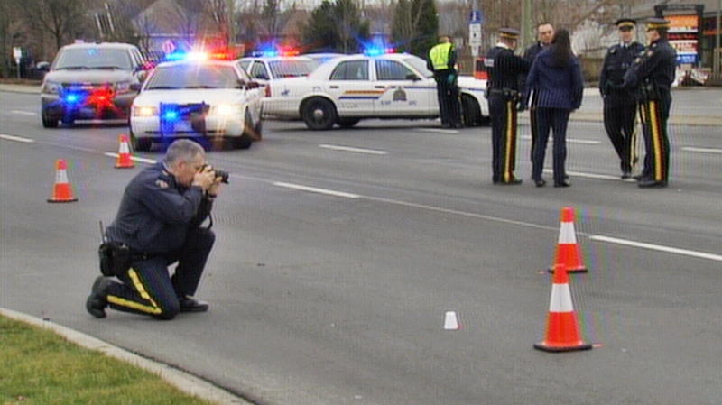 An RCMP officer photographs the scene of a police-involved shooting at the intersection of 200th Street and 72nd Avenue in Langley. A suspect fled following the incident and has not yet been found. Dec. 25, 2013. (CTV)