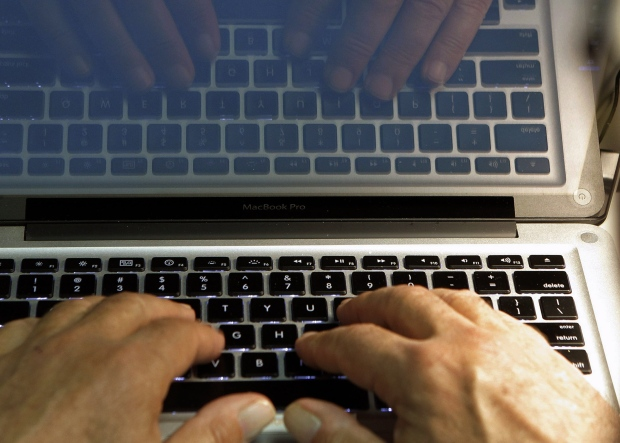 In this Wednesday, Feb. 27, 2013 photo illustration, hands type on a computer keyboard in Los Angeles. (AP Photo/Damian Dovarganes, File)