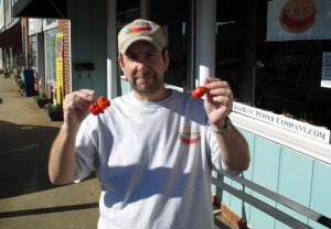 In this Dec. 12, 2013 photo, Ed Currie holds Carolina Reaper peppers, in Fort Mill, S.C. Last month, The Guinness Book of World Records decided Currie's peppers were the hottest on Earth, ending a more than four-year drive to prove no one grows a more scorching chili. (AP Photo/Jeffrey Collins)