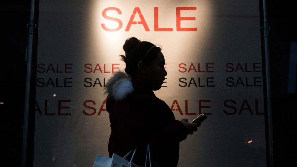 A shopper carries her bags after a visit to the Boxing Day sales at the Eaton Centre in Toronto on Thursday, December 26, 2013. (Chris Young / THE CANADIAN PRESS)