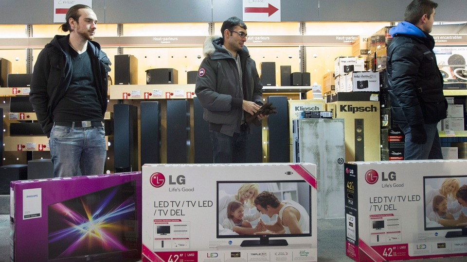 Shoppers wait in line to pay for big screen televisions at an electronics store on Boxing Day in Montreal, Thursday, December 26, 2013. (Graham Hughes / THE CANADIAN PRESS)