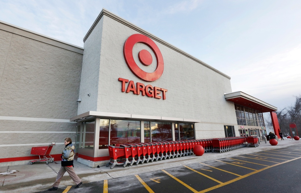 In this Dec. 19, 2013 file photo, a passer-by walks near an entrance to a Target retail store in Watertown, Mass.  (AP Photo/Steven Senne, File)