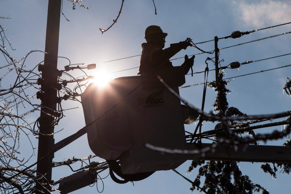 A Toronto Hydro line worker works to restore power to a house in a Scarborough neighbourhood on Friday, Dec. 27, 2013. (Chris Young / THE CANADIAN PRESS)