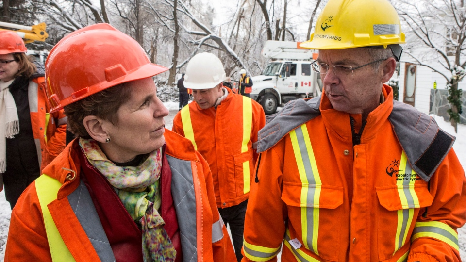Ontario Premier Kathleen Wynne, left, talks with Anthony Haines, CEO of Toronto Hydro, right, as she visits a Toronto Hydro crew who are working to restore power in a Scarborough neighbourhood on Friday, December 27, 2013. (Chris Young / THE CANADIAN PRESS)