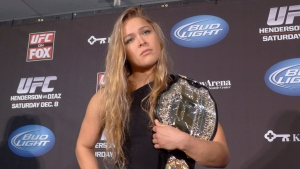 (Rowdy) Ronda Rousey shows off her UFC bantamweight championship belt, on Dec. 6, 2012 in Seattle. THE CANADIAN PRESS/Neil Davidson