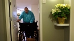 In this Dec. 21, 2013 photo, George Warren pulls his wheelchair through his apartment's front door at Village Crossroads, an affordable senior community in Nottingham, Md. Warren's wheelchair is too wide for the doorway and he can't afford a narrower model, so he folds it before carefully pulling it through. (AP / Patrick Semansky)