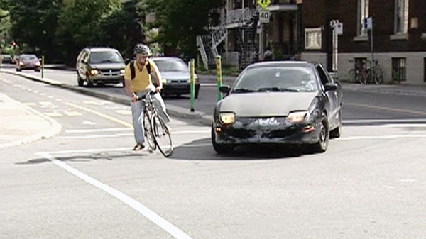 A cyclist narrowly avoids being struck by a vehicle in the streets of Montreal in this undated photo.