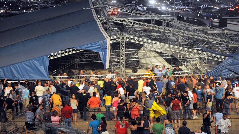Fans waiting to see Sugarland attempt to hold up the stage after high winds blew the stage over at the Indiana State Fair Grandstands in Indianapolis, Saturday, Aug. 13, 2011. (AP / The Indianapolis Star, Matt Kryger)