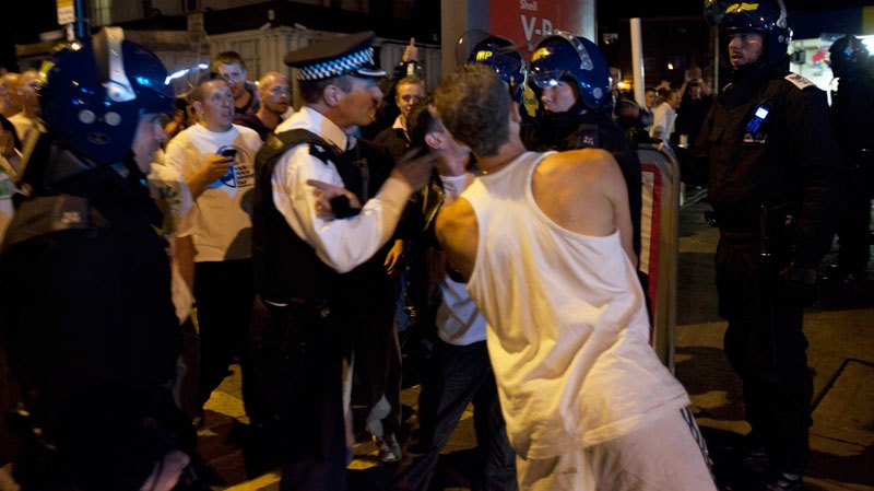 Police officers scuffle with men as members of the community march to reclaim their streets on Tuesday Aug. 9, 2011 in Enfield, North London. (AP / Karel Prinsloo)