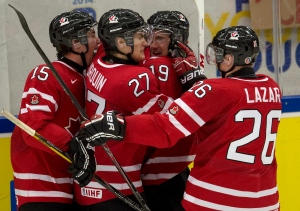 Canada forward Nic Petan (19) is congratulated by teammates Derrick Pouliot (15), Jonathan Drouin (27) and Curtis Lazar (26) after scoring the game-winning goal during third period action against Slovakia at the IIHF World Junior Hockey Championships in Malmo, Sweden on Monday, Dec. 30, 2013. (Frank Gunn / THE CANADIAN PRESS)