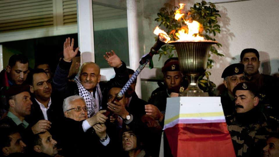 Palestinian President Mahmoud Abbas lights a torch while joined by released Palestinian prisoners, marking the 49th anniversary of the Fatah movement, during a welcome ceremony after their arrival at the Palestinian headquarters, in the West Bank city of Ramallah, Tuesday, Dec. 31, 2013. (AP / Nasser Nasser)
