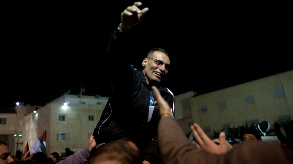 A released Palestinian prisoner is carried by his family following a welcome ceremony and celebrations after arriving at the Palestinian headquarters in the West Bank city of Ramallah, Tuesday, Dec. 31, 2013. (AP / Nasser Nasser)