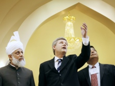Prime Minister Stephen Harper gestures to a chandelier with His Holiness Hadbrat Mirza Masroor Ahmed, left, and MP Deepak Obhrai at the opening of the Baitun Nur Mosque in Calgary on Saturday, July 5, 2008. (Jeff McIntosh / THE CANADIAN PRESS)
