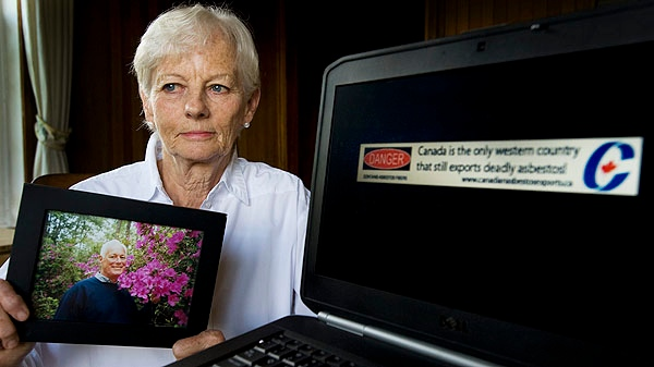 Michaela Keyserlingk holds a picture of her husband Robert as she poses for a photograph at her home in Labelle, Que., Saturday, August 13, 2011. On her laptop is the banner ad she created to put pressure on Canada's Conservative government to stop the production and export of Asbestos. (The CANADIAN PRESS/Graham Hughes)