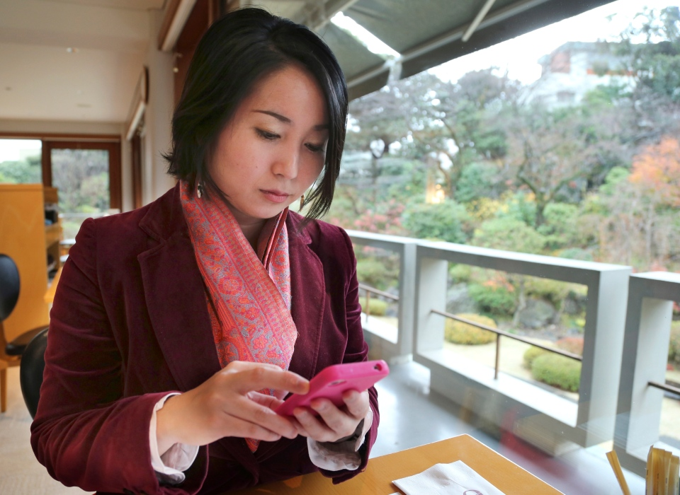 In this Friday, Dec. 20, 2013 photo, Emi Shitara checks her mobile phone during an interview with The Associated Press in Tokyo. (AP Photo/Koji Sasahara)
