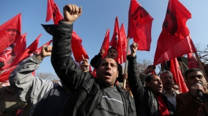 Palestinians chant slogans and wave Palestinian and red flags, background, that represent the Palestinian Marxist-Leninist secular political and military organization, during a demonstration organized by the Democratic Front for the Liberation of Palestine, against resuming peace talks with Israel in Gaza City, Thursday, Jan. 2, 2014. (AP Photo/Hatem Moussa)