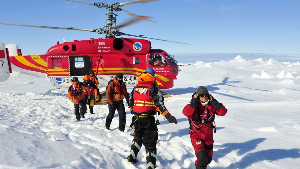 In this photo provided by China's Xinhua News Agency, the first group of passengers who were aboard the trapped Russian vessel MV Akademik Shokalski, arrive at a safe surface off the Antarctic, Thursday, Jan. 2, 2014. (AP / Xinhua, Zhang Jiansong)