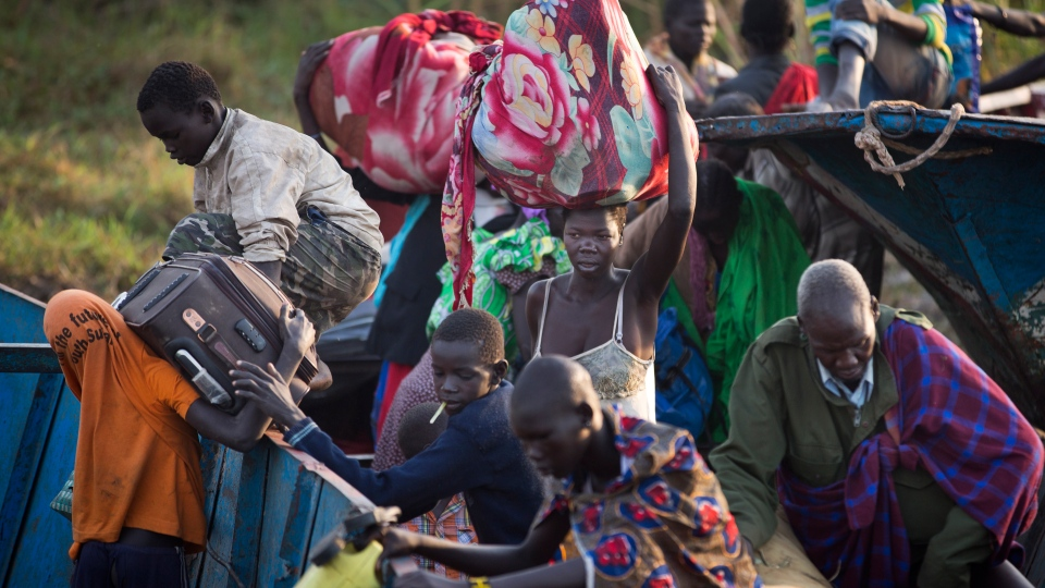 Displaced people get off a river barge from Bor, some of the thousands who fled the recent fighting between government and rebel forces in Bor by boat across the White Nile, in the town of Awerial, South Sudan Thursday, Jan. 2, 2014. (AP / Ben Curtis)
