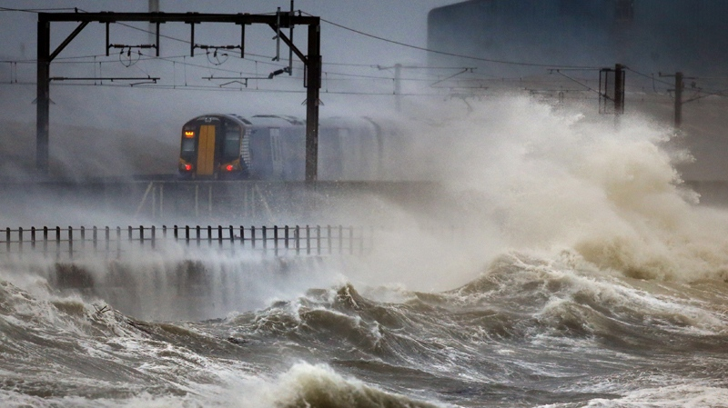 A train passes along the coast at Saltcoats in Scotland, Friday, Jan. 2014, as Britain is braced for the worst as a combination of high tides, heavy rains and strong winds are expected to bring yet more severe flooding to many parts of the country. (AP / PA, Danny Lawson)